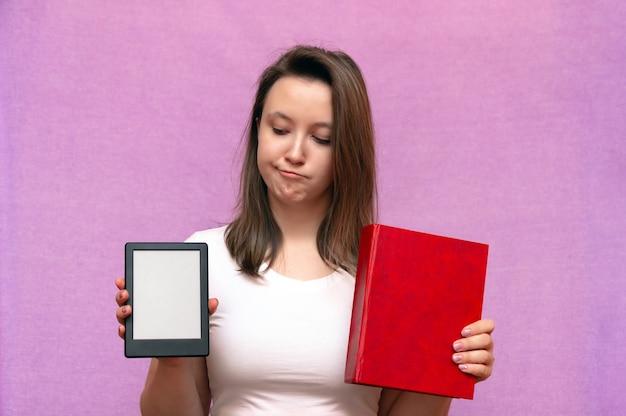 Frau, die zwischen papierbuch und elektronischem gerät wählt