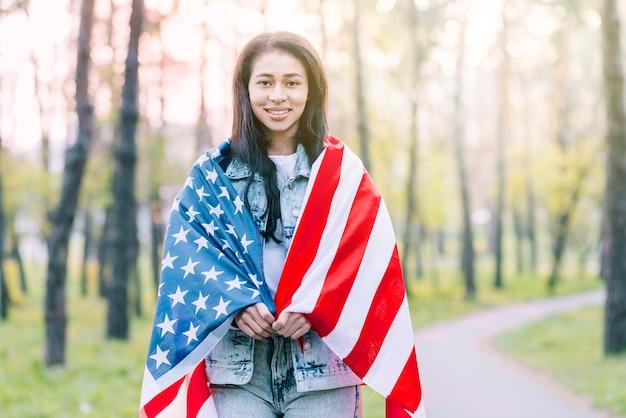 Frau draußen eingewickelt in der amerikanischen flagge