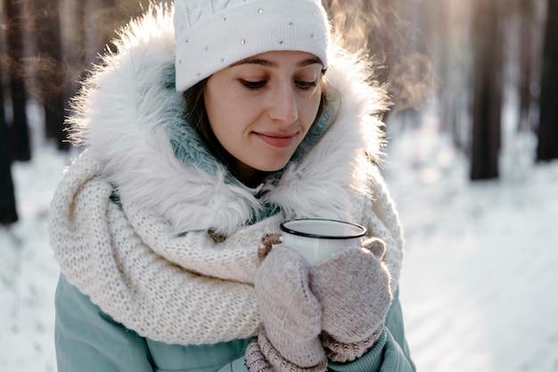Frau draußen im winter, die eine tasse tee hält