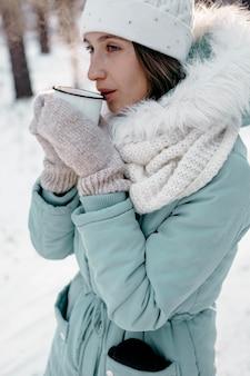 Frau draußen im winter mit einer tasse tee