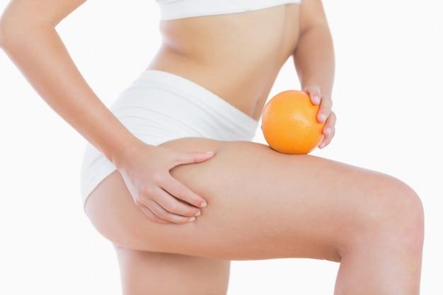 Frau drückt cellulite haut am oberschenkel, wie sie orange hält