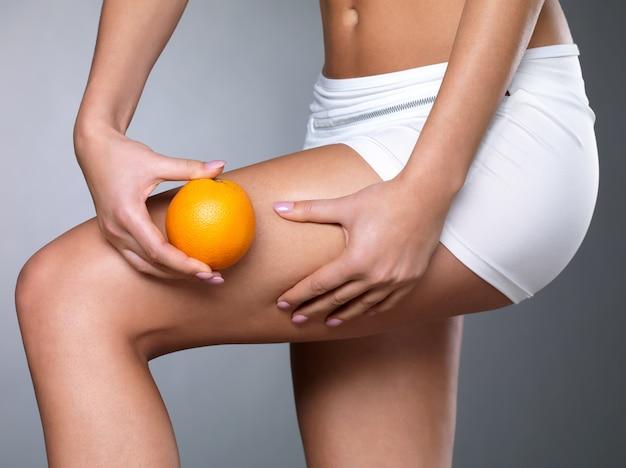Frau drückt cellulite-haut auf ihren beinen - nahaufnahme auf weißem raum
