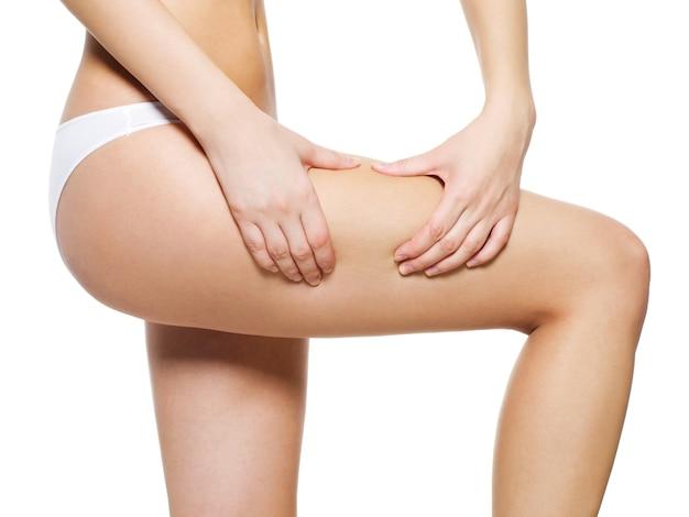 Frau drückt cellulite-haut auf ihren beinen