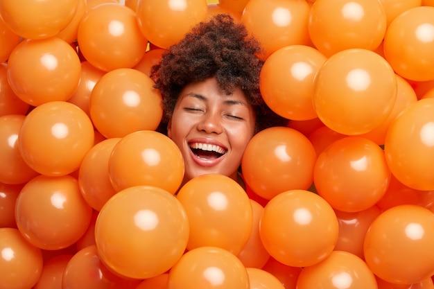 Frau drückt positive emotionen aus hält die augen geschlossen lächelt breit von aufgeblasenen luftballons umgeben