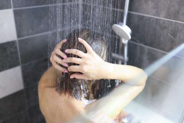 Frau duscht morgens und abends im badezimmer