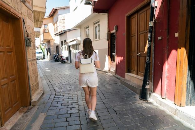 Frau, eine moderne reisende, geht durch die straßen des alten antalya im stadtteil kaleichi in der türkei. gemütliche altstadt, ein guter ort zum reisen und spazierengehen, blick von hinten.