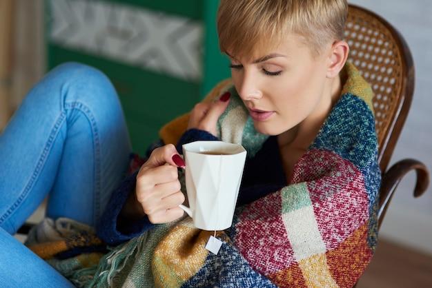 Frau eingehüllt in eine decke, die am wintertag tee trinkt