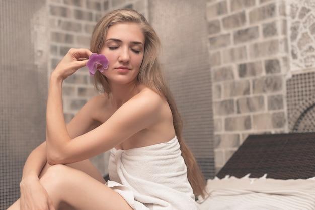 Frau eingewickelt im tuch, das orchidee in ihrer hand sich entspannt am badekurort hält