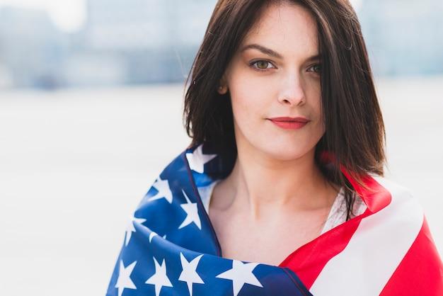 Frau eingewickelt in der amerikanischen flagge, die patriotisch kamera betrachtet
