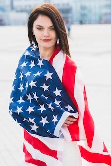 Frau eingewickelt in der amerikanischen flagge mit patriotismus