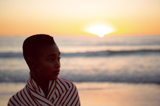 Frau eingewickelt in der decke, die auf dem strand steht