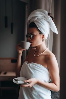 Frau eingewickelt in einem tuch nach einem trinkenden kaffee der dusche