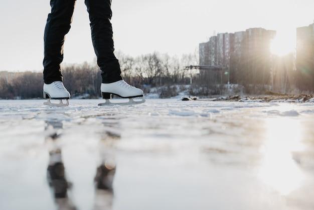Frau eislaufen am gefrorenen see im wintertag. outdoor-sportaktivitäten im winter