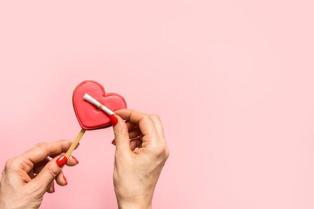Frau entfaltet eine liebesnotiz auf herzförmigem keks auf rosa