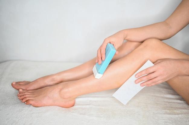 Frau entfernt haare an ihren beinen mit wachs