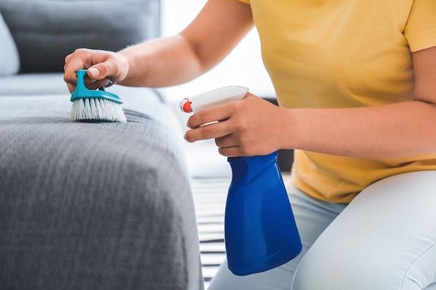 Frau entfernt schmutz vom sofa zu hause
