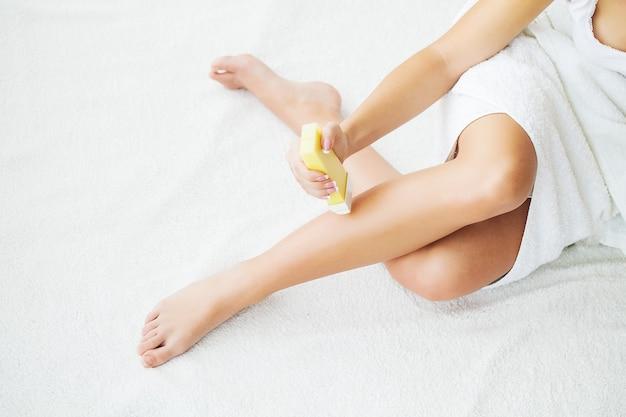 Frau entfernt wachs mit haaren von den beinen.