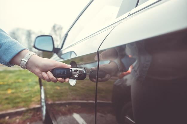 Frau entriegelt, öffnet das auto durch den fahrzeugschlüssel, sicherheitskonzept, transport