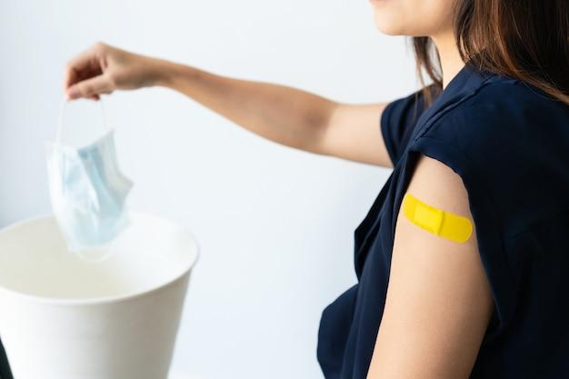 Frau entsorgt mundschutz nach covid19-impfstoffinjektion