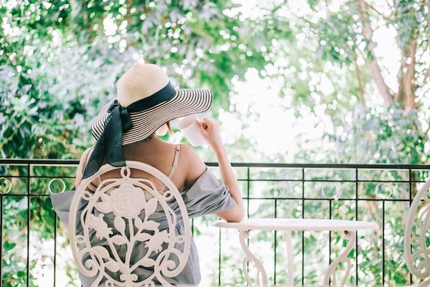Frau entspannen sich und trinkendes kaffee- und teesonnensitzen im freien im sonnenscheinlicht, das ihren morgenkaffee genießt