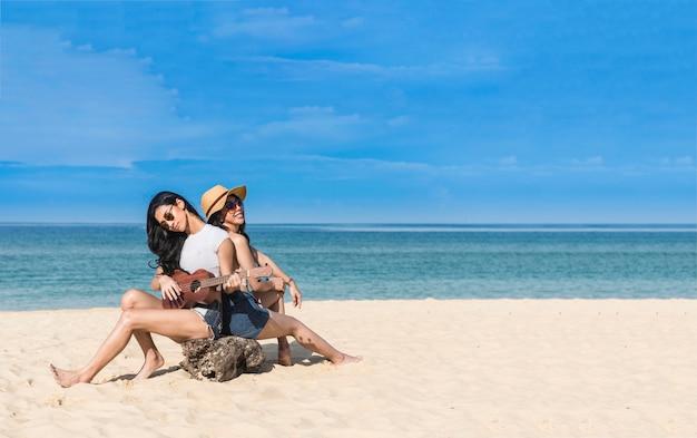 Frau entspannen und genießen sie ukulele am strand für urlaub sommer urlaub spielen
