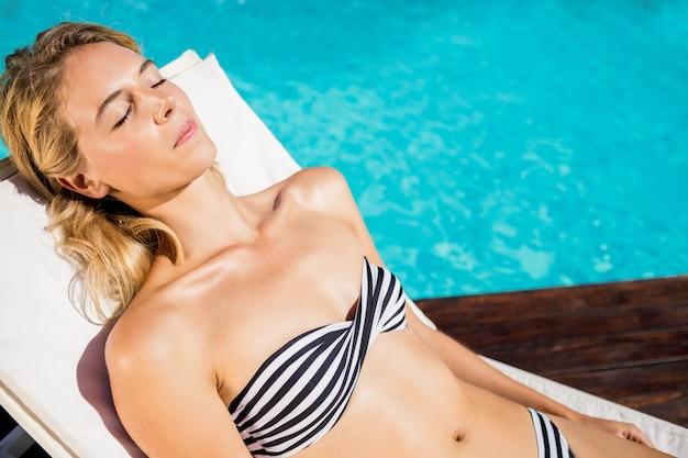 Frau entspannend auf liegestuhl am pool