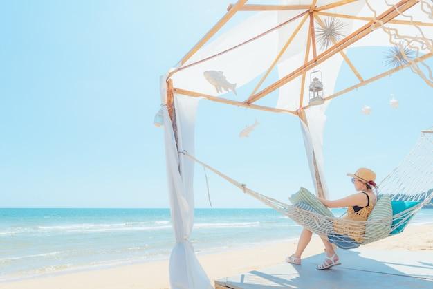 Frau entspannend in der hängematte am strand