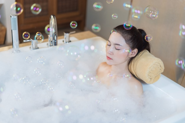 Frau entspannt mit geschlossenen augen in der badewanne