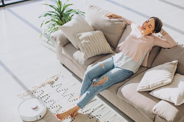 Frau entspannt sich auf dem sofa, während roboterstaubsauger hausarbeit macht house