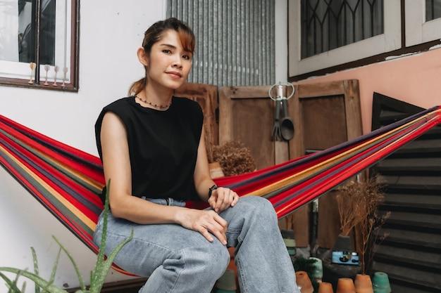 Frau entspannt sich auf der hängematte außerhalb ihres hauses im sommeraufenthaltskonzept