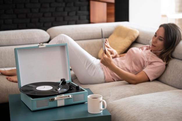 Frau entspannt sich zu hause beim hören von vinylmusik