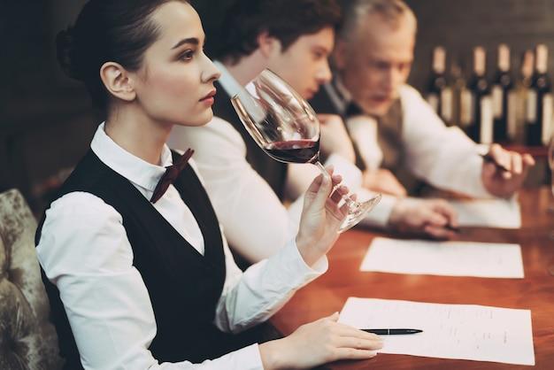 Frau erforscht geschmack des weins im restaurant. weinprobe.