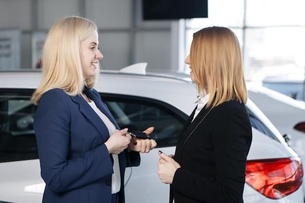 Frau erhält autoschlüssel von einem händler