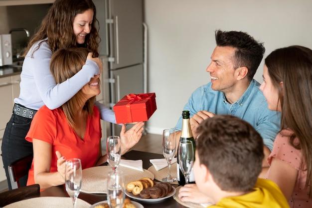 Frau erhält geschenk beim abendessen umgeben von familie