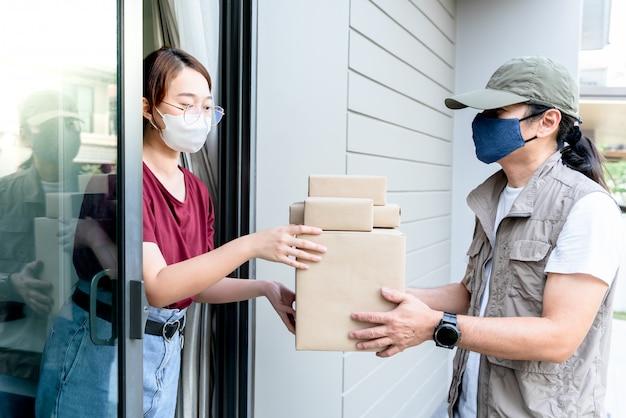 Frau erhält paket vom lieferboten, den sie online bestellt hat