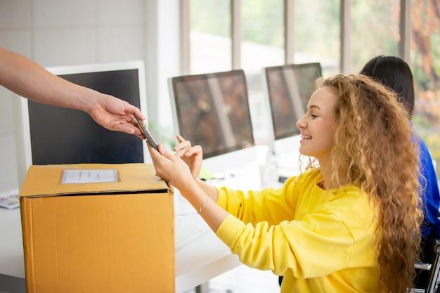 Frau erhält paket vom lieferboten und unterschreibt auf tablette