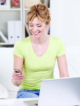 Frau erhalten eine gute nachricht auf modilem telefon, das mit laptop zu hause sitzt