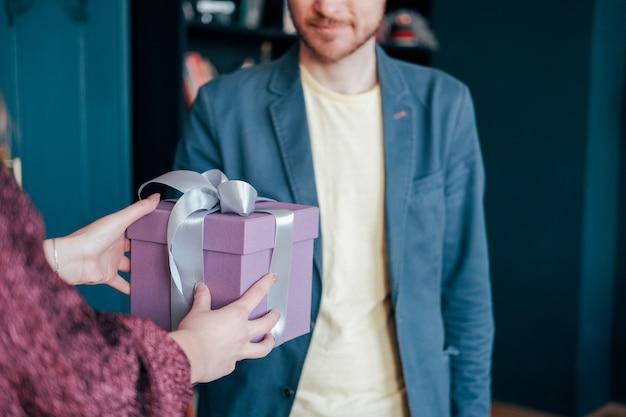 Frau erhalten geschenkbox mit grauem silbernem band vom jungen attracrive mann auf blauem hintergrund