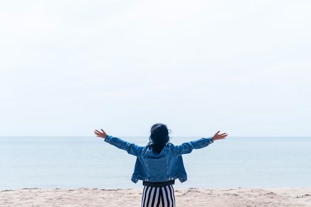 Frau erheben hände zum himmel fühlen sich frei und freiheit himmel und meer.