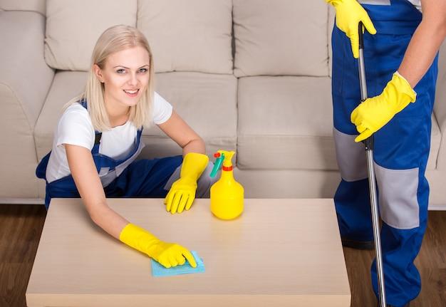 Frau erledigt etwas reinigungsarbeit im haus.