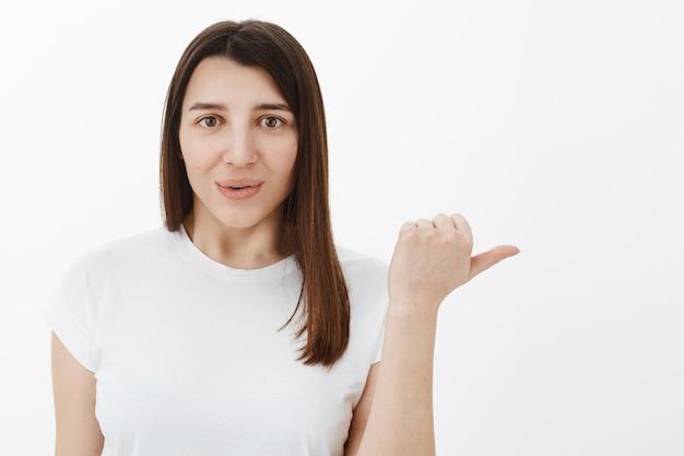 Frau erzählt über fantastisches produkt, das mit dem daumen rechts anzeigt, um sich lächelnd anzusehen, lippen vor erstaunen und interesse faltend, empfehlend zu beobachten und zu versuchen, gegen weiße wand zu posieren
