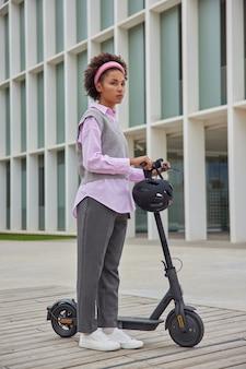 Frau fährt elektro-tretroller durch die stadt erreicht das notwendige ziel schnell posiert auf der straße trägt lässige, bequeme kleidung, schaut nachdenklich nach vorne