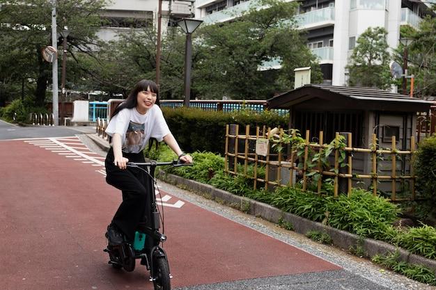 Frau fährt elektroroller in der stadt
