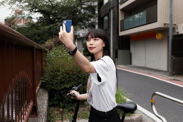 Frau fährt fahrrad in der stadt und macht selfie and