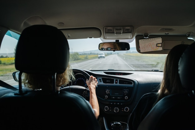 Frau fährt ihr auto durch eine landschaft. rücksitzansicht. sie trägt eine sonnenbrille, ihr gesicht spiegelt sich in einem spiegel.