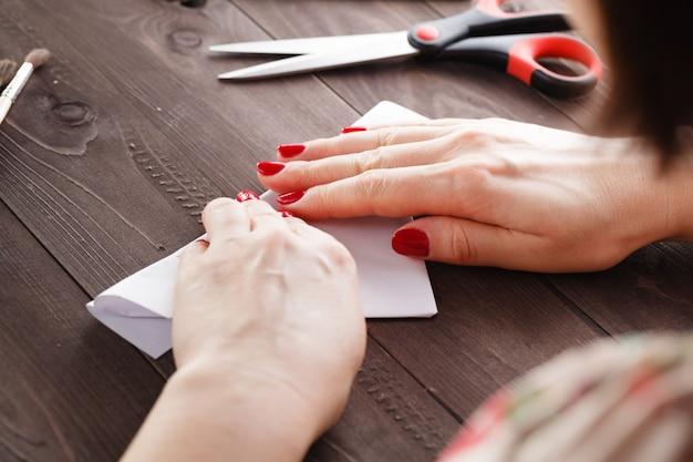 Frau falten blatt papier, während origami tun