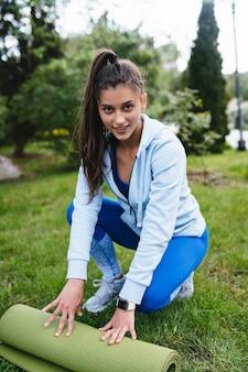 Frau faltrolle fitness oder yogamatte nach dem training im park. gesundes lebenskonzept