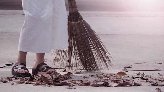 Frau fegt trockene blätter auf dem zementboden mit langem holzbesen und hält den außenbereich sauber