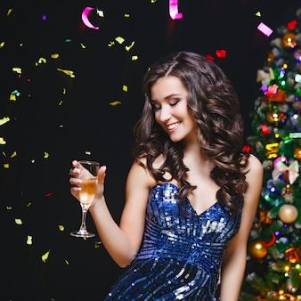 Frau feiern. ferien leute. schönes mädchen mit dem perfekten make-up, das glas champagner hält