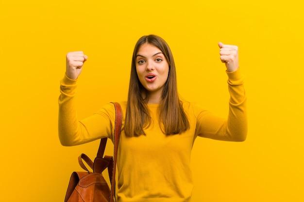 Frau feiert einen unglaublichen erfolg wie eine gewinnerin, sieht aufgeregt und glücklich aus und sagt, nimm das!